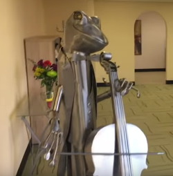 Photograph of a metal frog playing a cello at The Changing Place.