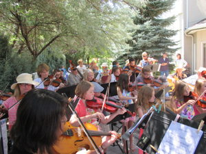 Photograph of Sue Jesch leading the Strings in the Summer musicians   last year at Sierra Place.
